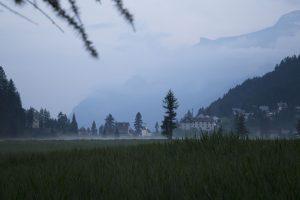 prato di montagna con nebbia e case sullo sfondo