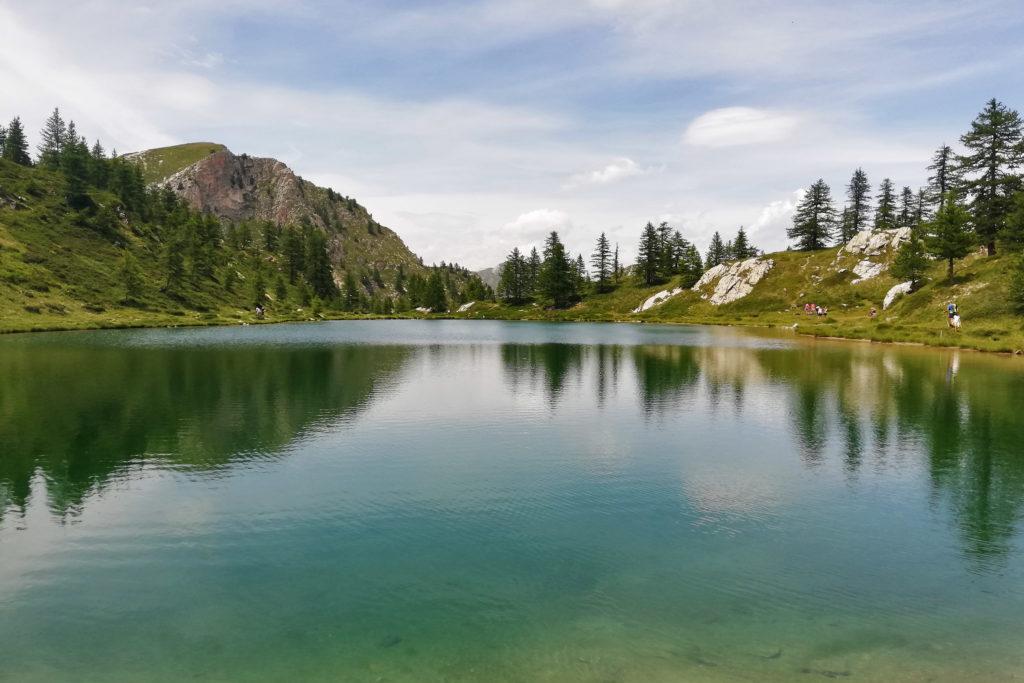 Lago di montagna con larici a specchio nell'acqua