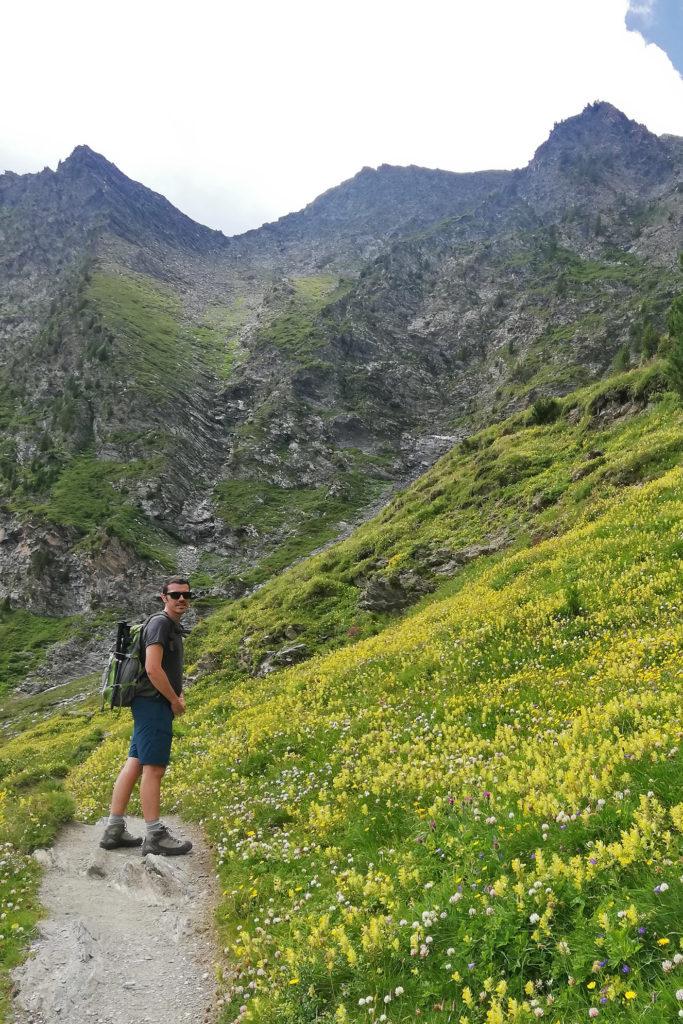 ragazzo su sentiero alpino in fiore